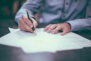A business person writing on a piece of paper in an interview.