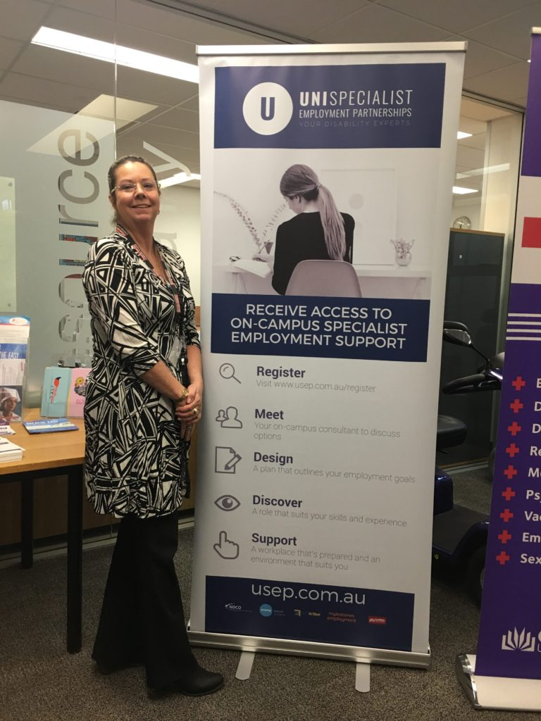 Photo of Natalie standing next to a pull up banner of USEP - Consultant from Mylestones Employment based at Griffith, Gold Coast. Natalie is ready to work with university students with disability.