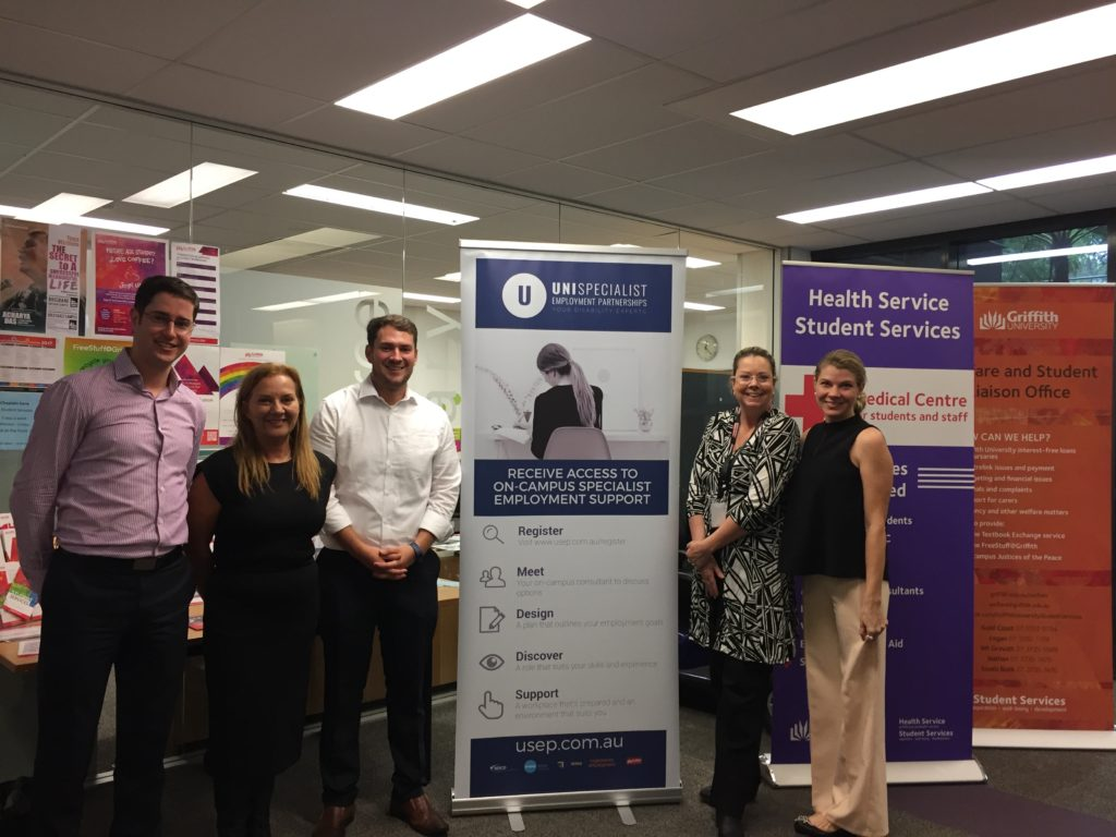 A photo of 5 people standing with a pull up banner of USEP - University Specialist Employment Partnerships