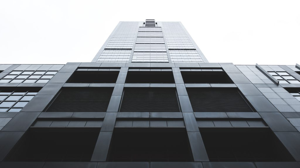 A photo of looking up at a large grey building into a white sky.