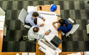 A birds eye view of 3 people around a table looking at a schematic of a building.