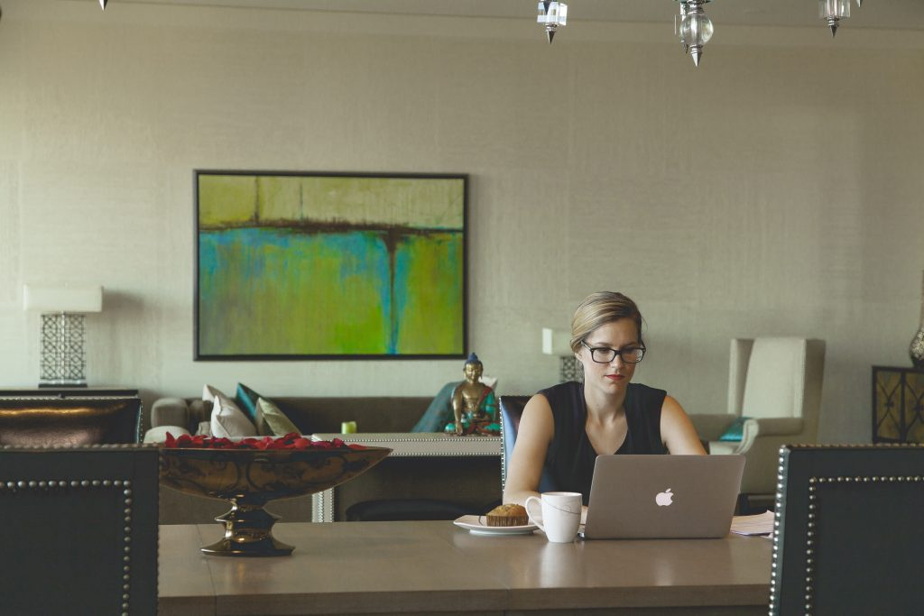 A photo of a blonde lady sitting at a desk with a laptop by herself, with a coffee.
