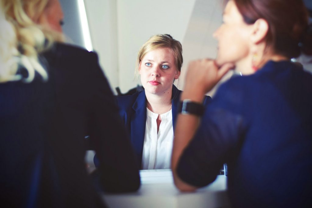 A blonde woman is pictured across the table from two managers, looking concerned.