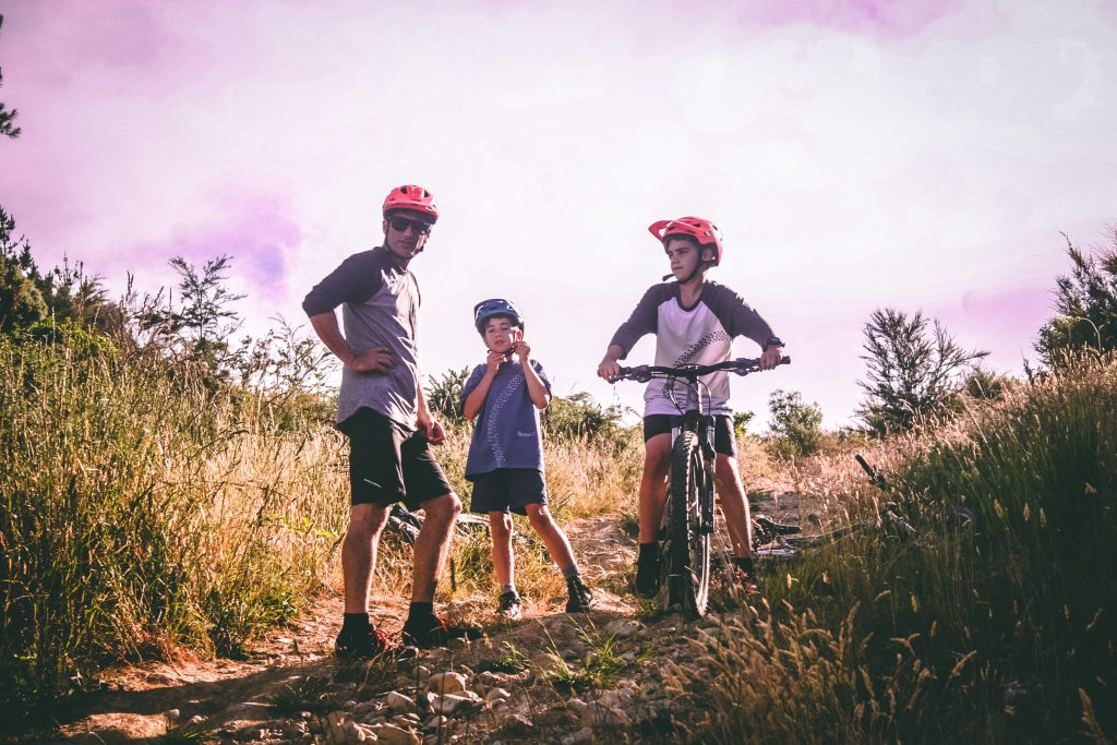 A photo of an adult and two boys with helmets on, with push bikes on a mountain.