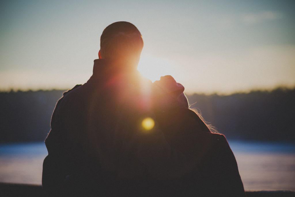 A silhouette of a couple looking into the sunset, leaning toward each other.